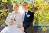 Groom with bride are looking ahead. Sunny autumn. — Stock Photo