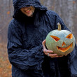 Stock Photo: Stranger with covered face keeps pumpkin