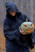Stranger with covered face keeps pumpkin — Stock Photo