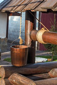 Wooden well. Bucket on a rope — Stock Photo