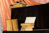 Old books lay on the piano — Stock Photo
