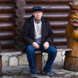 Elderly man sitting close to a wooden statue — Stock Photo