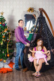 Family before Christmas fireplace — Stock Photo