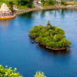 Island with tropical greenery in blue lake — Stock Photo #38656557