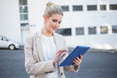 Smiling stylish businesswoman scrolling on digital tablet — Stock Photo