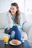 Smiling woman talking on the phone sitting on sofa — Stock Photo