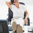 Relaxed businesswoman sitting at her desk with her feet up smiling at camera — Stock Photo #31540643