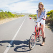 Happy young model posing while riding bike — Stock Photo