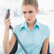 Frowning stylish businesswoman holding the phone — Stock Photo