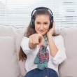 Peaceful cute model pointing at camera listening to music — Stock Photo
