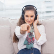 Peaceful cute model pointing at camera listening to music — Stock Photo #31543669