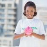 Happy volunteer holding piggy bank — Stock Photo #31544069