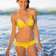 Cheerful gorgeous woman in yellow bikini bathing in the sea — Stock Photo