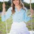 Smiling young model relaxing sitting on swing — Stockfoto