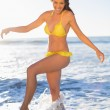 Happy gorgeous woman in yellow bikini having fun in the sea — Stock Photo