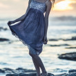 Beautiful young woman standing on rocks by the sea — Stock Photo