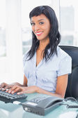 Cheerful businesswoman typing on a keyboard — Stock Photo