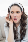 Pretty casual woman being surprised on the phone — Stock Photo