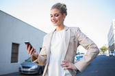 Smiling elegant businesswoman looking at her smartphone — Stock Photo