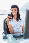 Charming businesswoman holding a mobile phone — Stock Photo