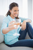 Smiling woman showing glass of white wine at camera — Stock Photo