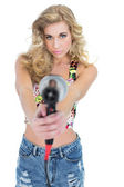 Unsmiling retro blonde woman pointing a hair dryer to the camera — Stock Photo