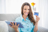Smiling woman holding tablet and showing her credit card — Stock Photo