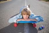 Funky young blonde lying on a road winking at camera — Stock Photo