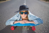 Funky young blonde lying on a deserted road — Stock Photo