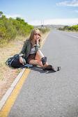物思いにふけるブロンドの女性が道端に座っています。 — ストック写真