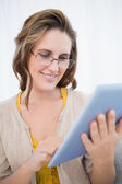 Smiling woman with glasses looking at tablet screen — Stock Photo