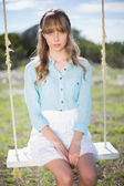Angelic natural young woman sitting on swing — Stock Photo