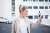 Angry stylish businesswoman shouting at her phone — Stock Photo