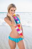 Cheerful sexy blonde in bikini wearing hawaii necklace — Stock Photo