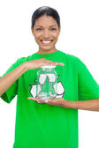 Cheerful model wearing recycling tshirt holding glass pot — Stock Photo