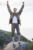Cheering woman standing on a rock — Stock Photo
