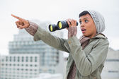 Shocked young model in winter clothes showing something in the sky — Stock Photo