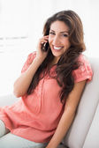 Jolie brunette assise sur son canapé sur un appel téléphonique — Photo