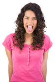Disgusted long haired brunette sticking her tongue out — Stock Photo