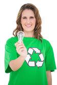 Smiling environmental activist holding light bulb looking at camera — Stock Photo