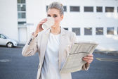 Serious stylish businesswoman drinking coffee — Stock Photo