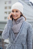 Smiling gorgeous woman wearing winter clothes having a call — Stock Photo