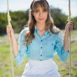 Peaceful young model relaxing while sitting on swing — Stockfoto