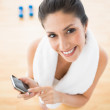 Fit woman using smartphone taking a break from workout smiling at camera — Stock Photo #31552681