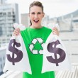 Cheerful woman in green recyling tshirt showing money bags — Stock Photo