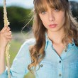 Natural young woman sitting on swing — Stockfoto