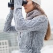 Gorgeous woman with winter clothes on looking through binoculars — Stock Photo #31553695