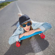 Funky young woman lying on a deserted road — Stock Photo