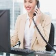 Smiling pretty businesswoman answering the phone — Stock Photo #31555165