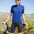 Woman holding and standing in front of bike — Foto de Stock